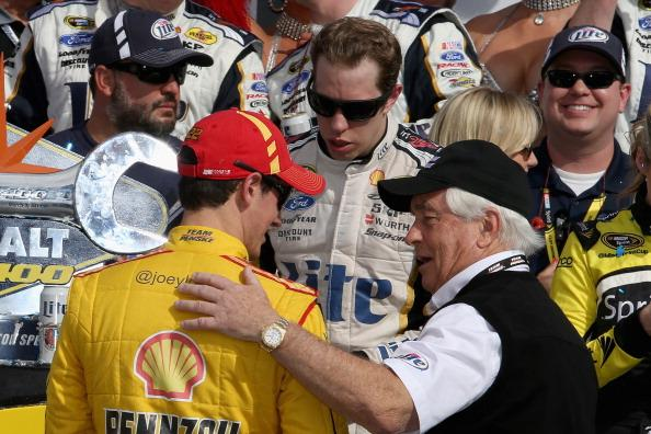 LAS VEGAS, NV - MARCH 09:  Joey Logano (left), driver of the #22 Shell-Pennzoil Ford, talks with Brad Keselowski, driver of the #2 Miller Lite Ford, and team owner Roger Penske in victory lane after Keselowski won the NASCAR Sprint Cup Series Kobalt 400 at Las Vegas Motor Speedway on March 9, 2014 in Las Vegas, Nevada.  (Photo by Todd Warshaw/Getty Images)