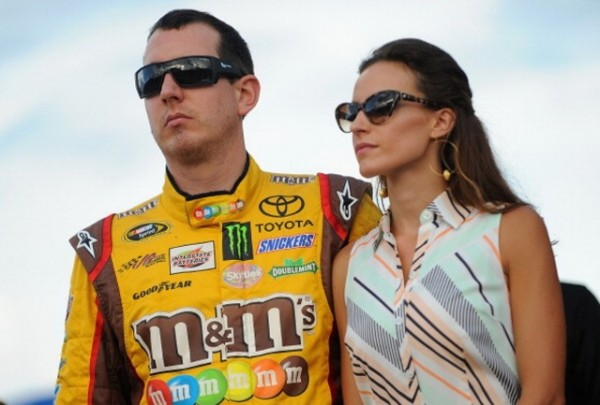 SPARTA, KY - JUNE 28 2014:  Kyle Busch, driver of the #18 M&M's Toyota, left, and wife Samantha Busch take part in pre-race ceremonies for the NASCAR Sprint Cup Series Quaker State 400 presented by Advance Auto Parts at Kentucky Speedway on June 28, 2014 in Sparta, Kentucky.  (Photo by Will Schneekloth/Getty Images)