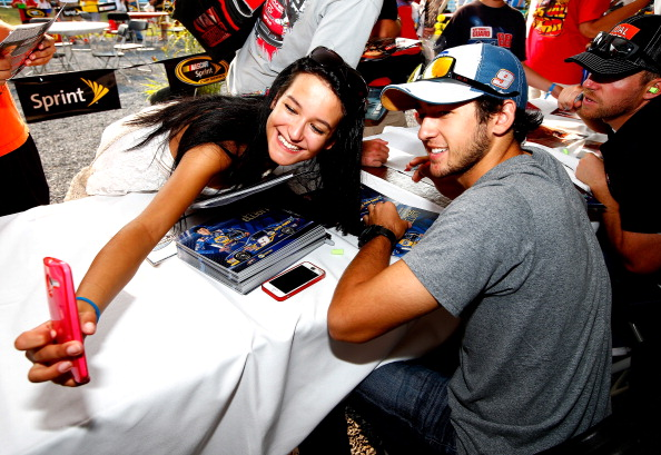 WATKINS GLEN, NY - AUGUST 08:  Chase Elliott, driver of the #9 NAPA Auto Parts Chevrolet, right, poses for a selfie with a NASCAR fan during an autograph session for the NASCAR Nationwide Zippo 200 at Watkins Glen International on August 8, 2014 in Watkins Glen, New York.  (Photo by Jared Wickerham/Getty Images)