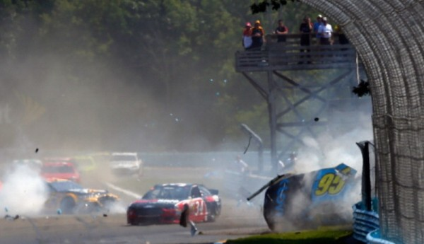 WATKINS GLEN, NY - AUGUST 10:  Michael McDowell, driver of the #95 K-Love Ford, and Ryan Newman, driver of the #31 Caterpillar Chevrolet, are involved in an on-track incident during the NASCAR Sprint Cup Series Cheez-It 355 at Watkins Glen International on August 10, 2014 in Watkins Glen, New York. The incident caused a red-flag period for repairs to a section of armco barrier.  (Photo by Tom Pennington/Getty Images)