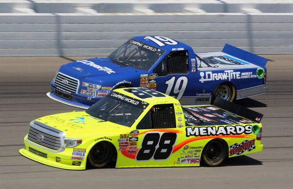 BROOKLYN, MI - AUGUST 16:  Matt Crafton, driver of the #88 Great Lakes Flooring/Menards Toyota, races with Joey Logano, driver of the #19 DrawTite Ford, during the NASCAR Camping World Truck Series Careers For Veterans 200 at Michigan International Speedway on August 16, 2014 in Brooklyn, Michigan.  (Photo by Jerry Markland/Getty Images)