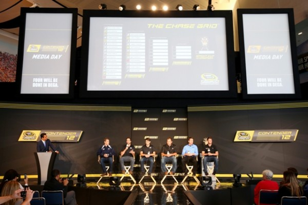 (L-R) ESPN's Kevin Negandhi introduces drivers Brad Keselowski, Jimmie Johnson, Jeff Gordon, Ryan Newman, Carl Edwards and Denny Hamlin as they speak to the media during a press conference for the NASCAR Sprint Cup Series Contender 12 at NASCAR Hall of Fame on October 1, 2014 in Charlotte, North Carolina.