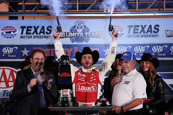 FORT WORTH, TX - NOVEMBER 02:  Jimmie Johnson, driver of the #48 Lowe's Red Vest Chevrolet, celebrates with Texas Motor Speedway President Eddie Gossage and AAA VIP Employee Recognition Winner David Tiger with pistols in Victory Lane after winning the NASCAR Sprint Cup Series AAA Texas 500 at Texas Motor Speedway on November 2, 2014 in Fort Worth, Texas.  (Photo by Chris Graythen/Getty Images for Texas Motor Speedway)