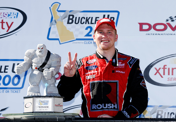 DOVER, DE - MAY 30:  Chris Buescher, driver of the #60 Roush Performance Products Ford, poses with the Miles the Monster trophy in Victory Lane after winning the NASCAR XFINITY Series Buckle Up 200 presented by Click It or Ticket at Dover International Speedway on May 30, 2015 in Dover, Delaware.  (Photo by Todd Warshaw/Getty Images)