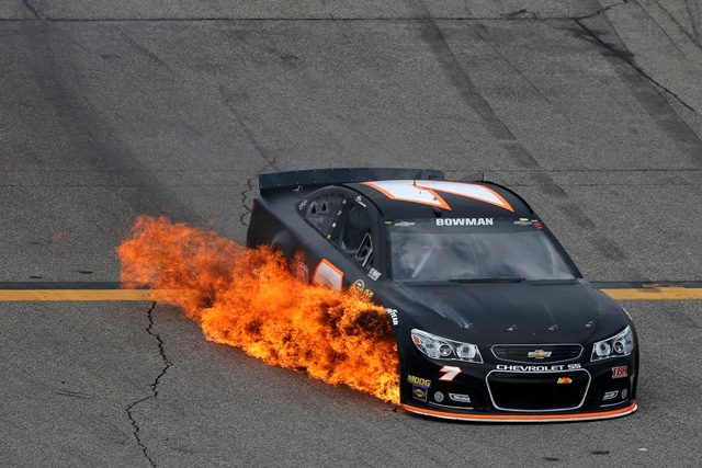 Alex Bowman drives the #7 Tommy Baldwin Racing Chevrolet off of pit road as his car catches fire during the NASCAR Sprint Cup Series 5-Hour ENERGY 301 at New Hampshire Motor Speedway on July 19, 2015 in Loudon, New Hampshire.