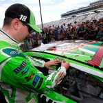 Kyle Busch, driver of the #18 Interstate Batteries Toyota, applies the winner's decal to his car after winning the NASCAR Sprint Cup Series 5-Hour ENERGY 301 at New Hampshire Motor Speedway on July 19, 2015 in Loudon, New Hampshire.