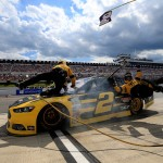 LONG POND, PA - AUGUST 02:  Brad Keselowski, driver of the #2 Alliance Truck Parts Ford, crashes into his crew on pit road during the NASCAR Sprint Cup Series Windows 10 400 at Pocono Raceway on August 2, 2015 in Long Pond, Pennsylvania.  (Photo by Chris Trotman/Getty Images)