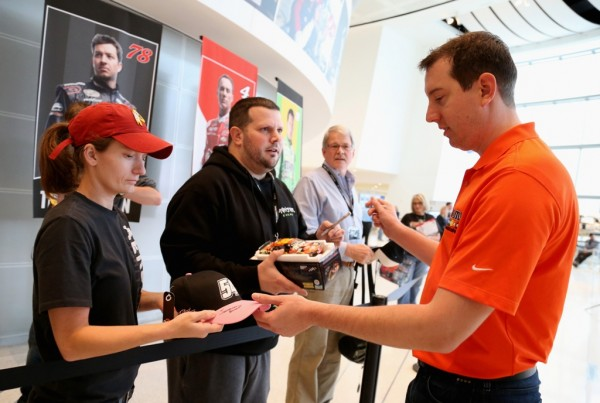 Kyle Busch signs for fans during The Chase for the NASCAR Sprint Cup Eliminator Round Media Day at NASCAR Hall of Fame on October 27, 2015 in Charlotte, North Carolina.