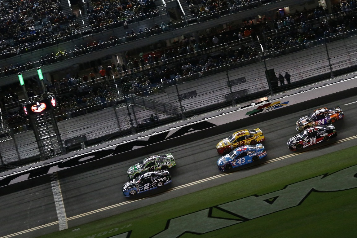 Brad Keselowski, driver of the #2 Detroit Genuine Parts Ford, and Kyle Busch, driver of the #18 Interstate Batteries Toyota, race in front of a pack of cars during the NASCAR Sprint Cup Series Coke Zero 400 Powered By Coca-Cola at Daytona International Speedway on July 2, 2016 in Daytona Beach, Florida.