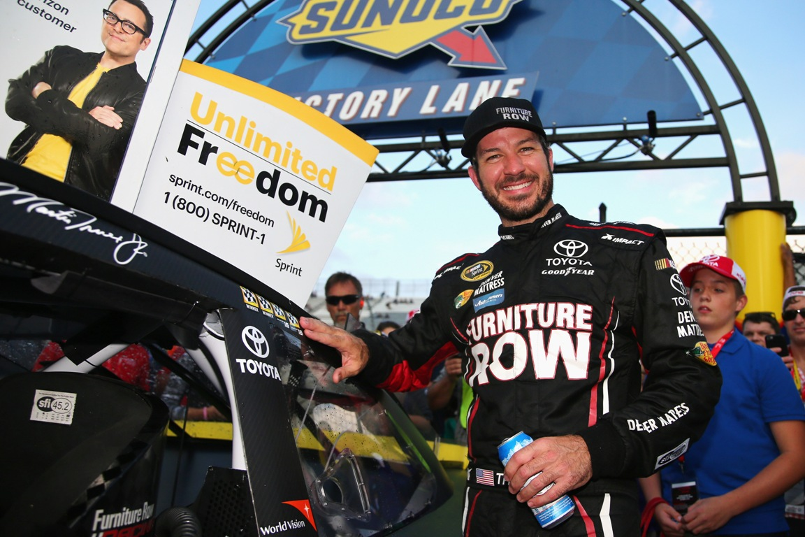 Martin Truex Jr., driver of the #78 Furniture Row/Denver Mattress Toyota, poses with the winner?s decal in Victory Lane after winning the NASCAR Sprint Cup Series Citizen Solider 400 at Dover International Speedway on October 2, 2016 in Dover, Delaware. (Getty Images)