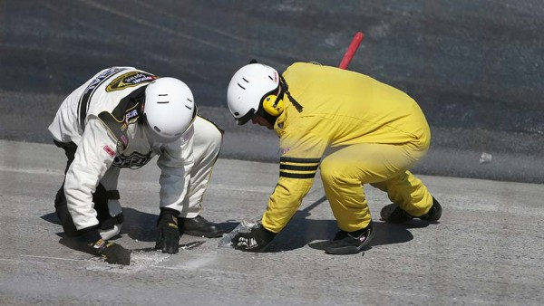 Officials work to patch a hole coming out of Turn 2 during the second red flag Sunday at Dover. (Getty Images)