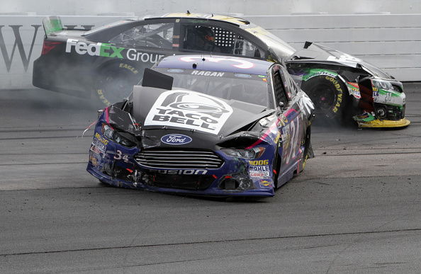 LOUDON, NH - SEPTEMBER 21:  David Ragan, driver of the #34 Taco Bell Ford, and Denny Hamlin, driver of the #11 FedEx Ground Toyota, are seen on the track after crashing during the NASCAR Sprint Cup Series Sylvania 300 at New Hampshire Motor Speedway on September 21, 2014 in Loudon, New Hampshire.  (Photo by Jerry Markland/Getty Images)
