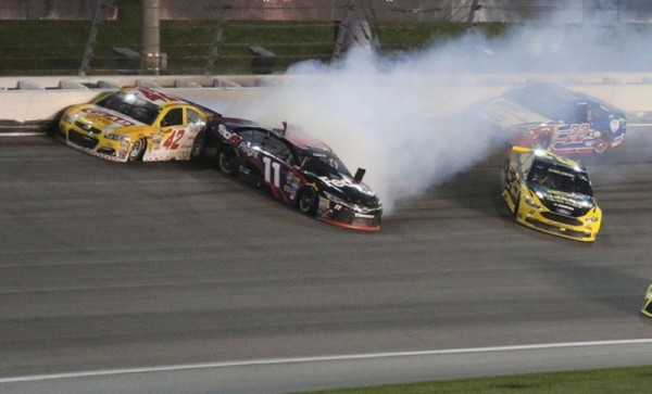 Denny Hamlin, driver of the #11 FedEx Express Freight Toyota, and Brad Keselowski, driver of the #2 Alliance Truck Parts Ford, wreck during the NASCAR Sprint Cup Series Go Bowling 400 at Kansas Speedway on May 7, 2016.