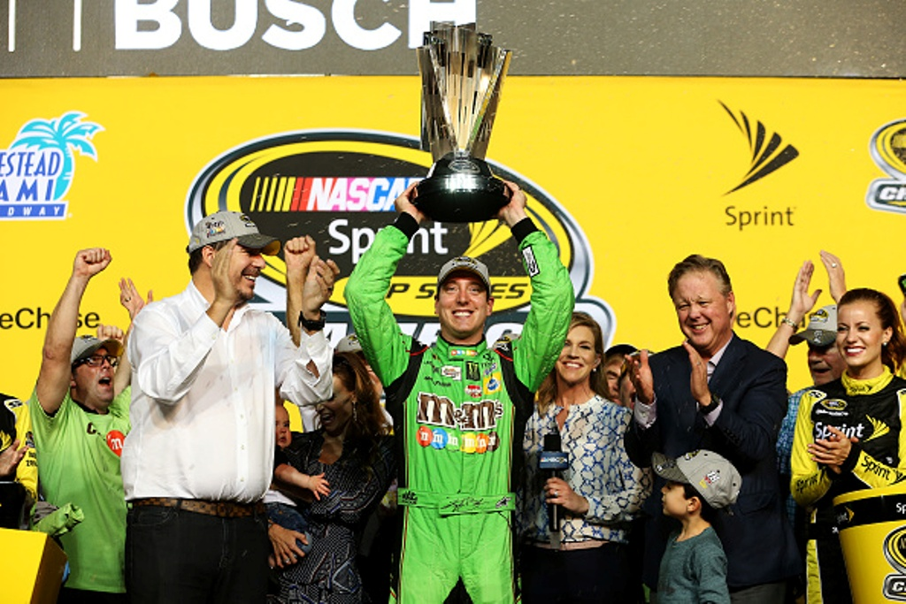 HOMESTEAD, FL - NOVEMBER 22: Kyle Busch, driver of the #18 M&M's Crispy Toyota, celebrates with the trophy in Victory Lane after winning the series championship and the NASCAR Sprint Cup Series Ford EcoBoost 400 at Homestead-Miami Speedway on November 22, 2015 in Homestead, Florida. (Photo by Chris Graythen/Getty Images)