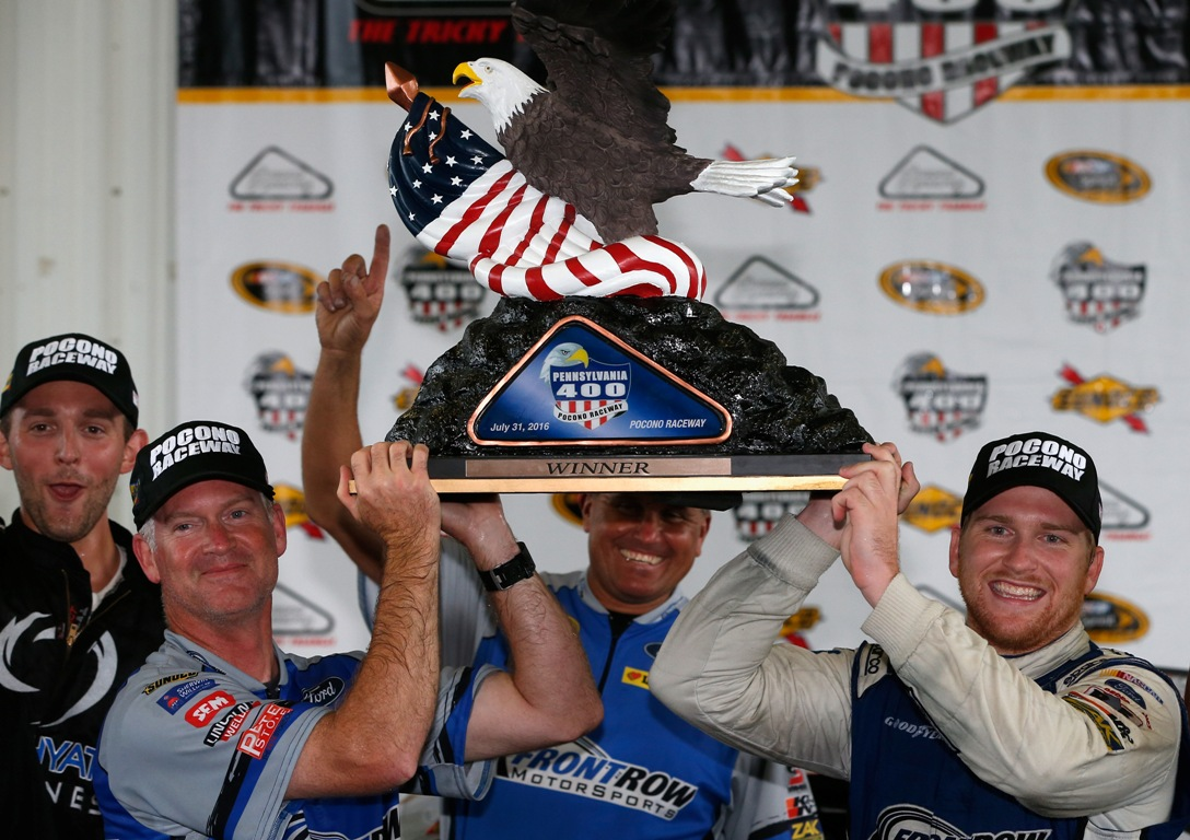 Chris Buescher, driver of the #34 Dockside Logistics Ford, and crew chief Bob Osborne pose with the trophy after winning the NASCAR Sprint Cup Series Pennsylvania 400 at Pocono Raceway on August 1, 2016 in Long Pond, Pennsylvania. The race was delayed due to inclement weather on Sunday, July 31. (Getty Images)